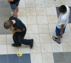 3 students using tile floor as a coordinate grid.